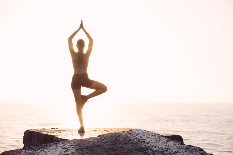 Woman Doing Yoga Pose Facing Sea